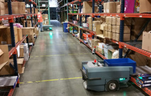 Robots picking order items from warehouse shelf.